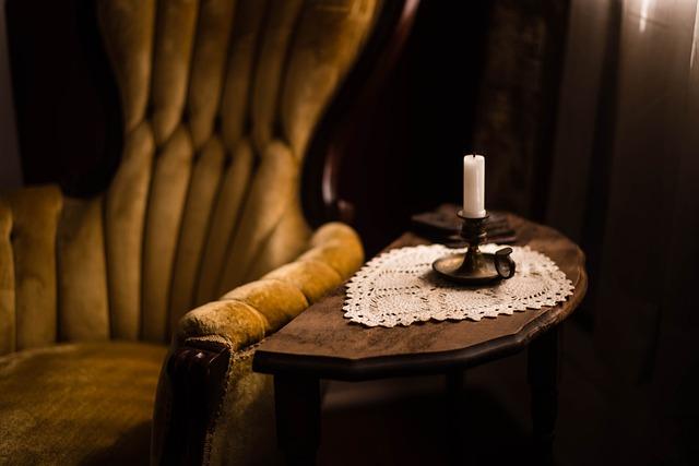 temná místnost s křeslem a svíčkou